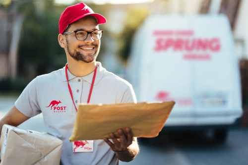 Smiling courier walking down the street and looking for right address for package delivery.